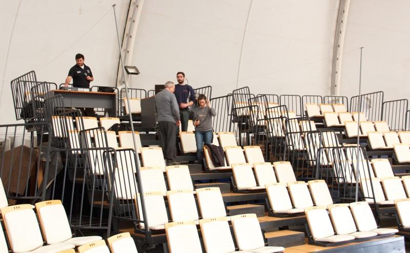 Se observa en el auditorio a cuatro perssonas, probando la colocación e instalción del aro magnético en el auditorio carpa compuesto por gradas y sillas en forma escalonada.