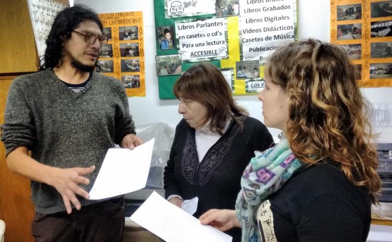 Se observa los miembros de la Biblioteca Parlante Nuevo Ser con integrantes de la Comisión de discapacidad sosteniendo distintos formatos de textos, en braille, escritos, etc.
